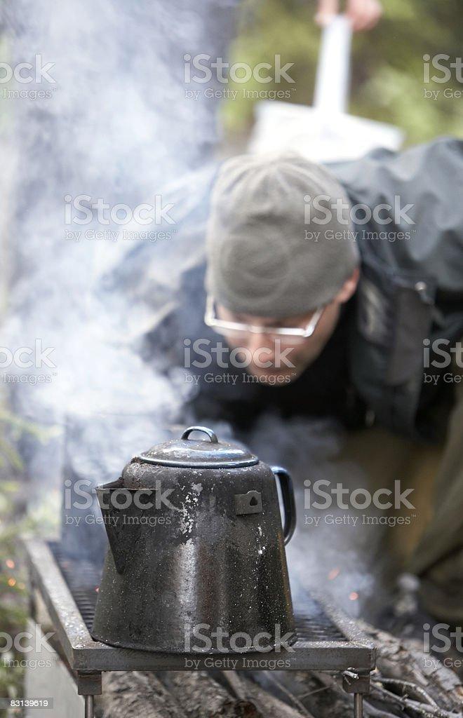 man near kettle on campfire royalty free stockfoto
