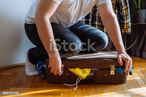 1067846662 istock photo man need help to close suitcase. overloaded bag with clothes. travel concept 939791416