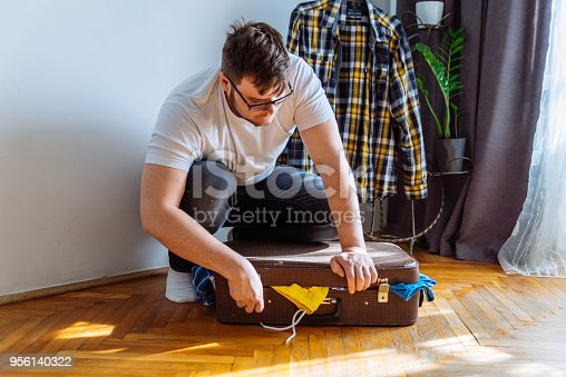 1067846662 istock photo man need help to close suitcase. overloaded bag with clothes. travel concept 956140322
