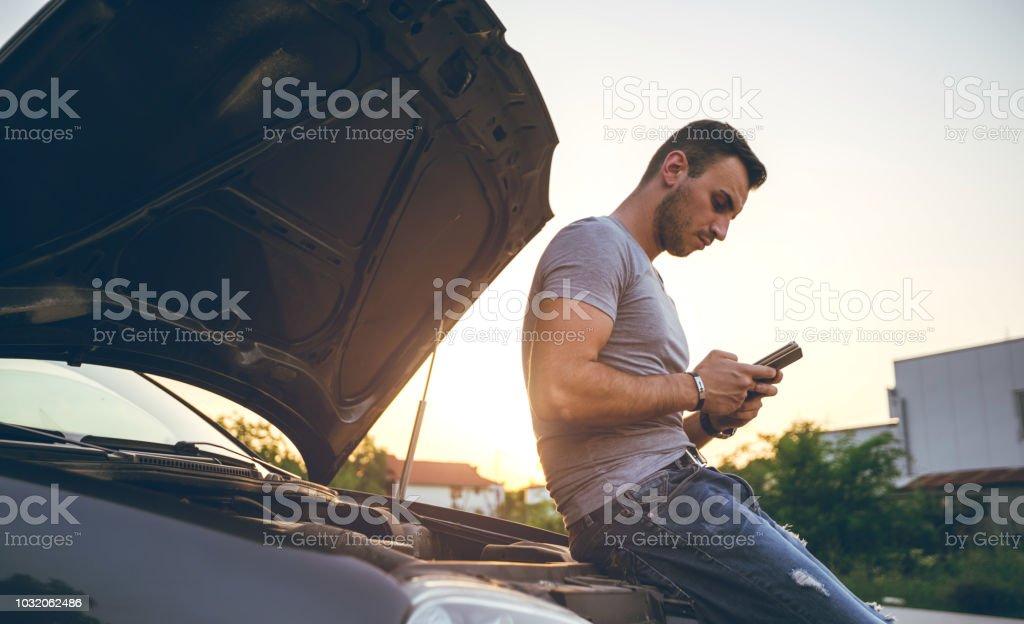 Man next to a broken down car stock photo