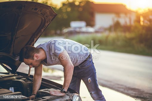 Young man is standing next to a broken down car, examining under the hood