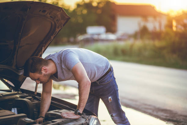 Man next to a broken down car stock photo