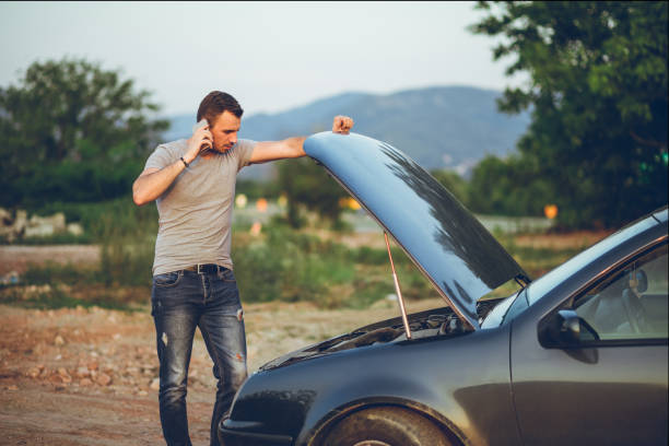 man next to a broken down car Young man calling for road assistance, standing next to a broken down car alongside stock pictures, royalty-free photos & images
