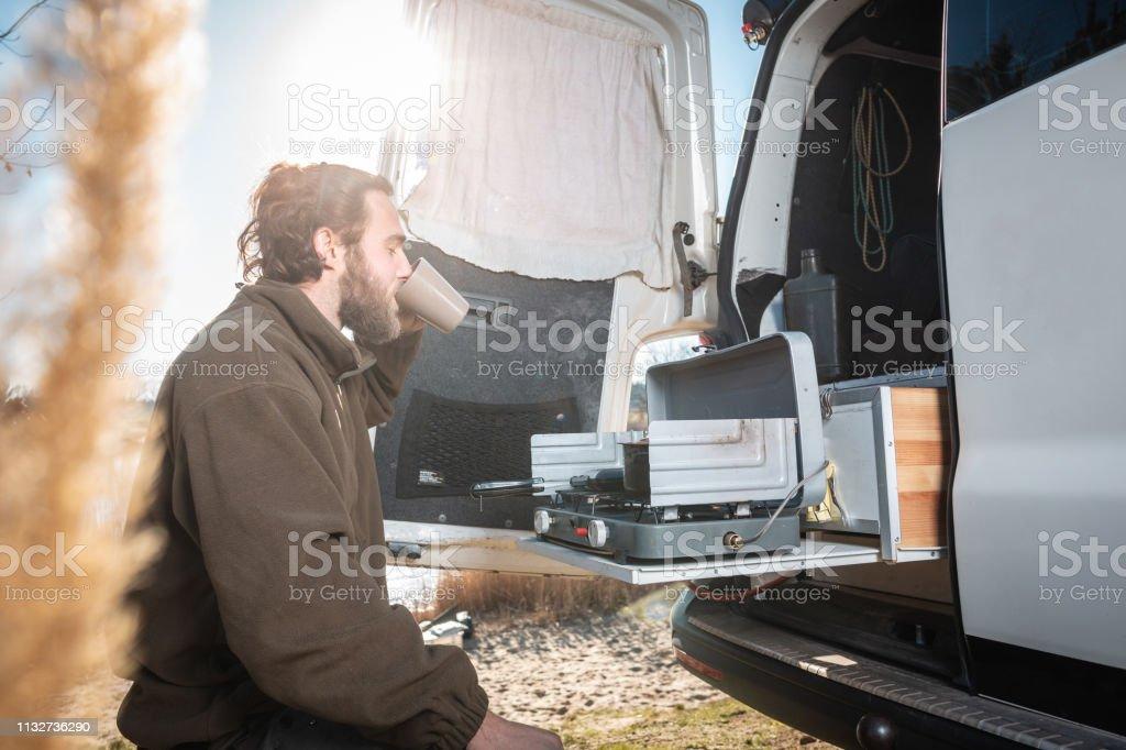 Mann neben seinem Wohnmobil mit einer Tasse Kaffee - Lizenzfrei Ausrüstung und Geräte Stock-Foto