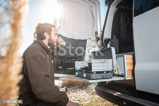 A young man with a beard enjoys being outside with his camper van. He is taking a sip out of a coffee cup.