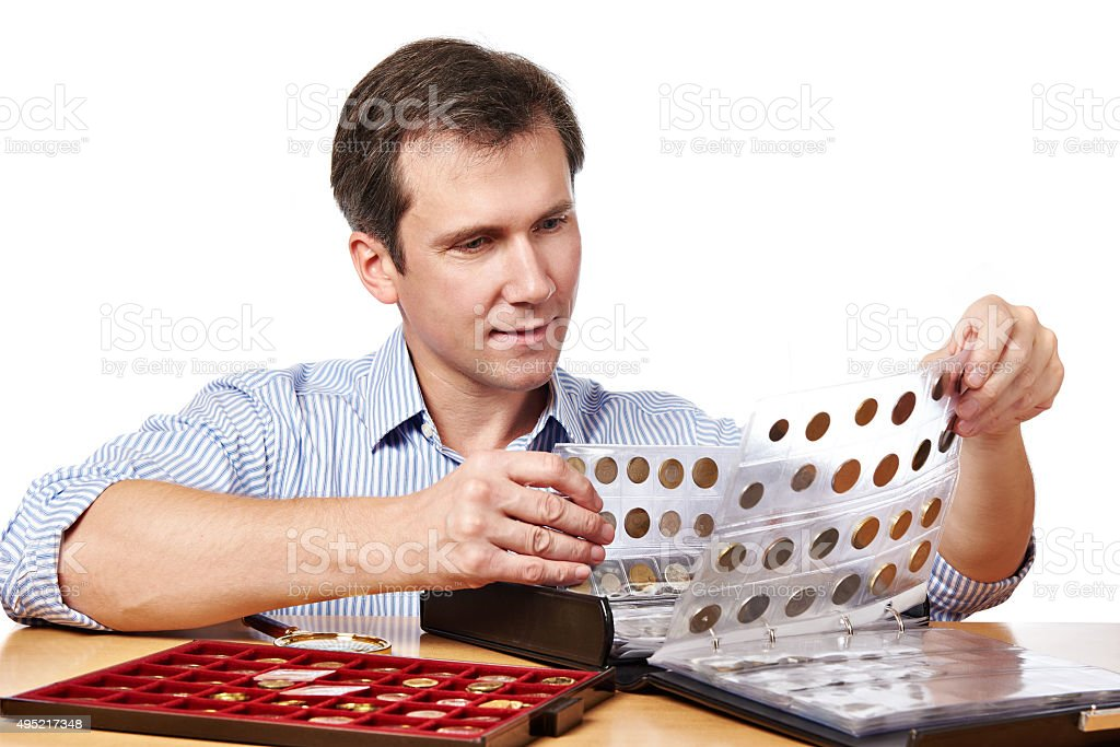 Man numismatist examines his collection of coin stock photo