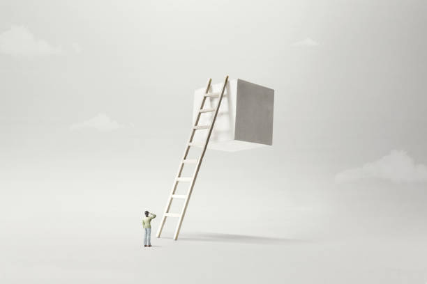 man observing white solid cube suspended in the air, surreal concept stock photo