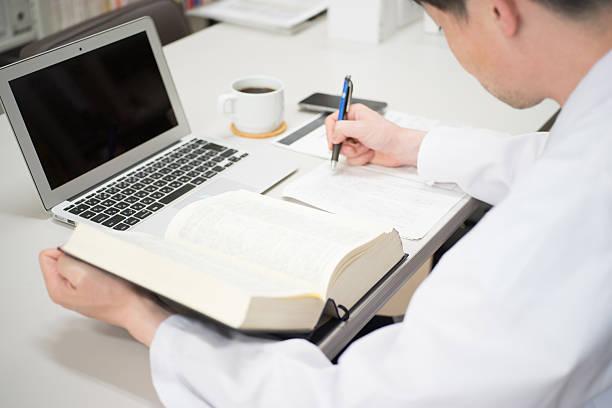 mann in einem weißen kimono machen schreibtisch arbeiten - online lexikon stock-fotos und bilder