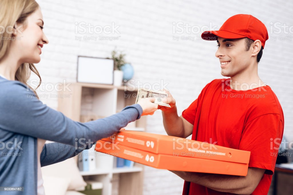 A man of Arab nationality works on the delivery of pizza. The girl...