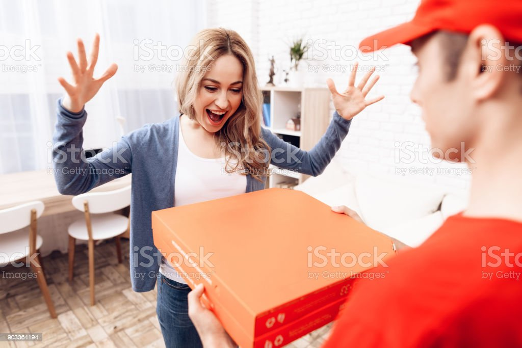 Man of Arab nationality works on the delivery of pizza. Pizza deliveryman brought an order to woman. stock photo