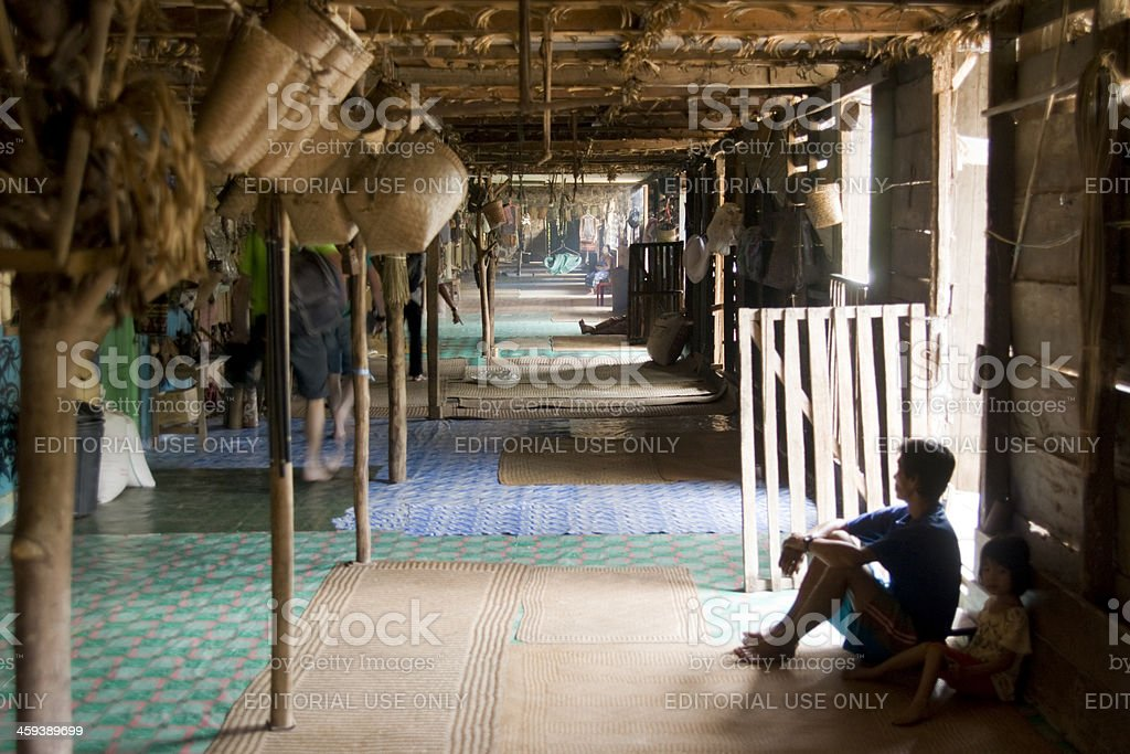 Man of Iban tribe sitting in Longhouse. stock photo