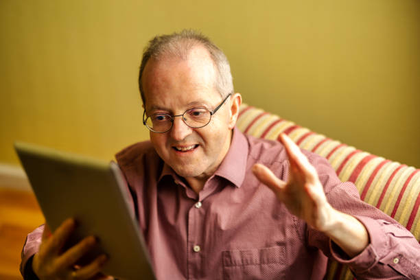 Man of middle-age sitting in the sofa of his living room at home, gesturing during a zoom video call meeting holding a tablet stock photo