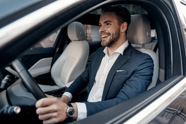 Man of style and status. Handsome young man in full suit smiling while driving a car driver occupation stock pictures, royalty-free photos & images