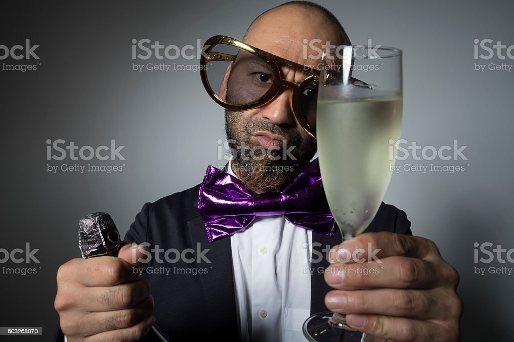 Man of sunglasses with a champagne glass in hand. stock photo