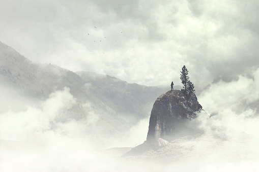 istock man of the top of the mountain in the fog 898700222