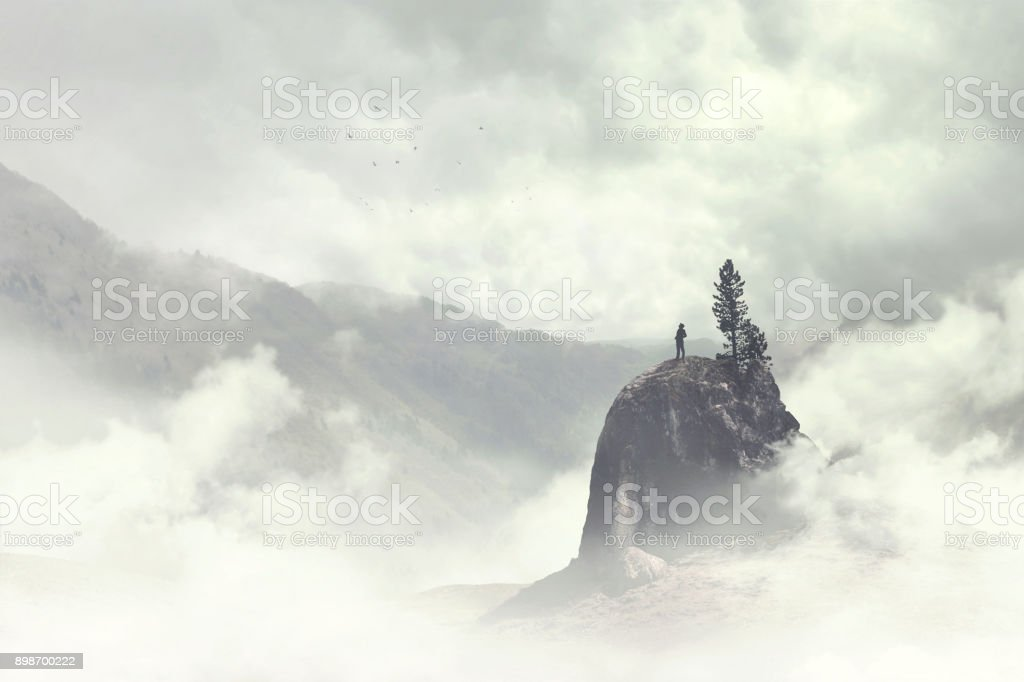 man of the top of the mountain in the fog stock photo