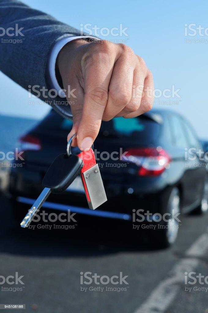 homem, oferecendo uma chave de carro para o observador - foto de acervo