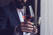 istock man offering a glass of rose wine 673388214