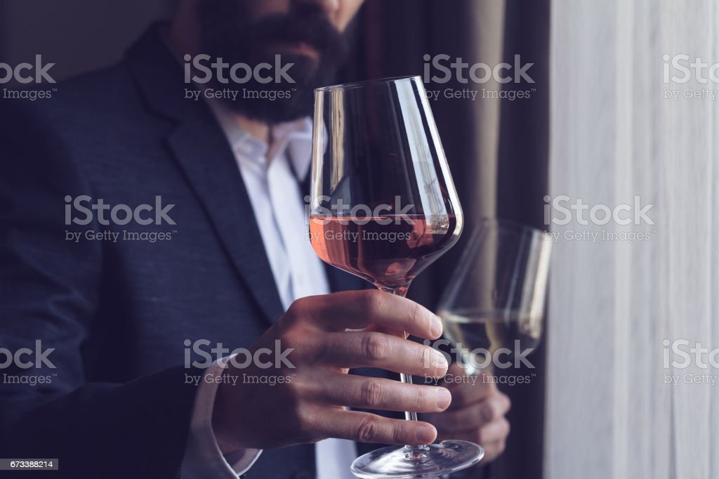 man offering a glass of rose wine stock photo