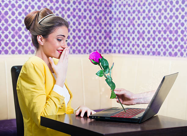 Man offering a rose to a beautiful woman over laptop screen stock photo