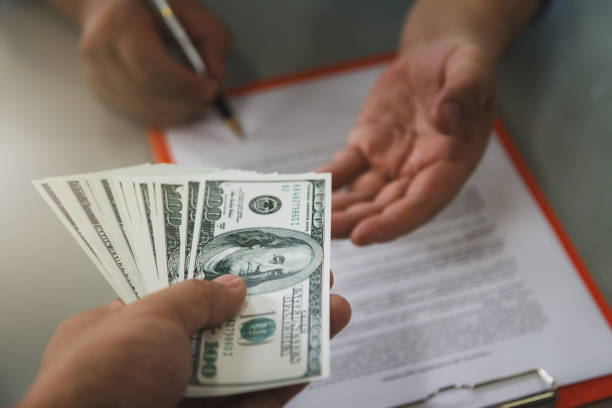 Man offering batch of hundred dollar bills. Close up of business man signing contract making a deal, business contract details. stock photo