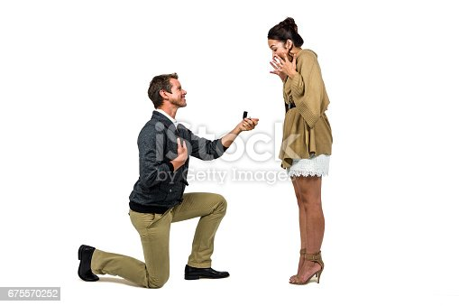 Man offering engagement ring to partner against white background