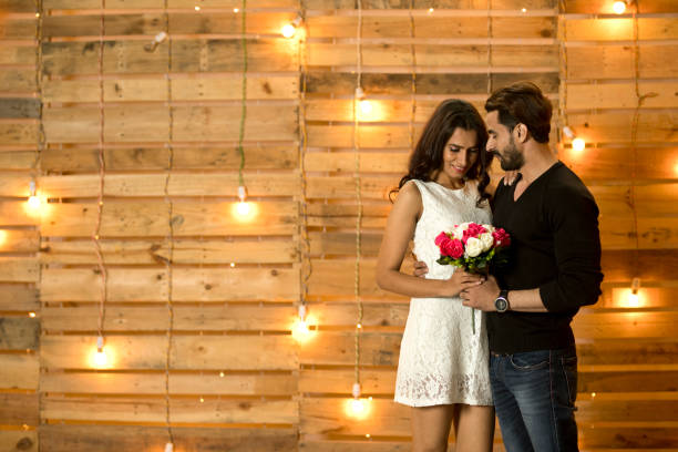 Man offering flowers to girlfriend Happy young man offering flowers to his girlfriend romance stock pictures, royalty-free photos & images
