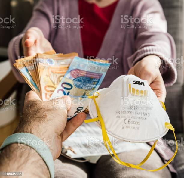 Man Offering Stack Of Money Banknotes For Surgical 3m Hand Sanding Respirator Stock Photo - Download Image Now