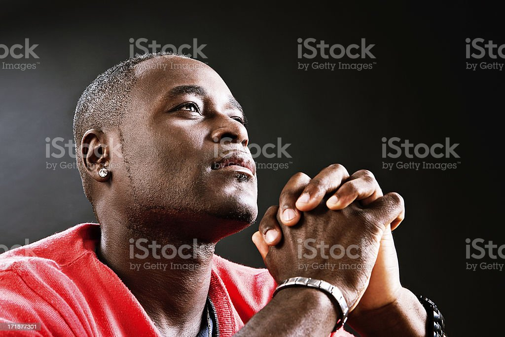 Man offers up heartful prayer, hands clasped stock photo