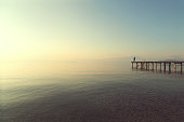 man on a boardwalk observing calm lake scenary at sunset