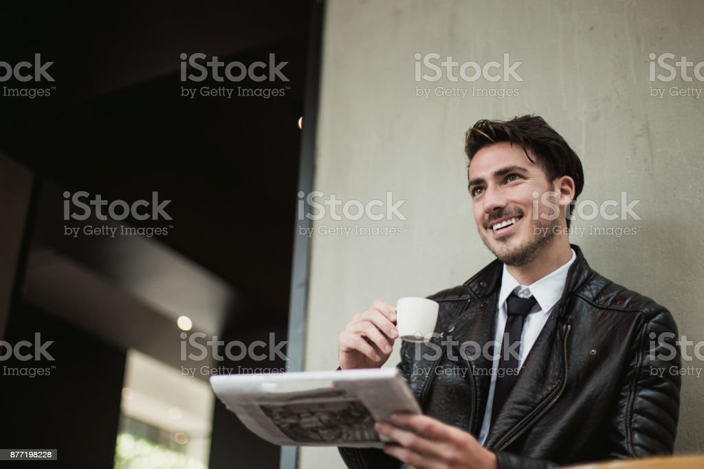 One man, sitting in cafe alone, drinking coffee, reading newspaper.