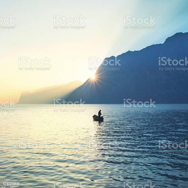 Photo of man on a canoe fishing under an amazing sunset