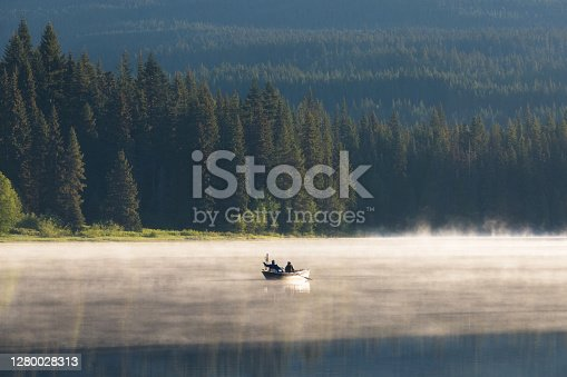 Man on a canoe. Mountains reflect over the calm waters of Sparks Lake at sunrise  in the Cascades Range in Central Oregon, USA in an early morning light. Morning mist rises from lake into trees.