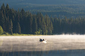 istock Man on a canoe. Mountains reflect over the calm waters of Sparks Lake at sunrise  in the Cascades Range in Central Oregon, USA in an early morning light. Morning mist rises from lake into trees. 1280028313
