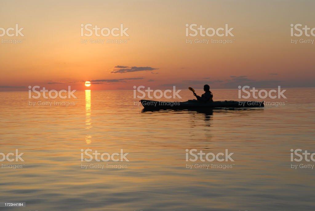 A man on a canoe on Lake Superior sunset stock photo