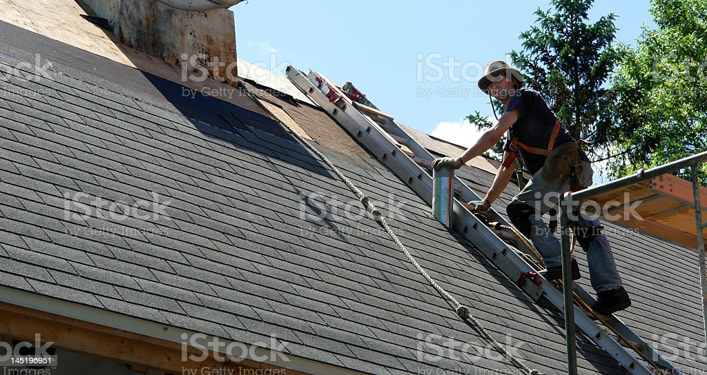 Man on a ladder replacing the roof stock photo