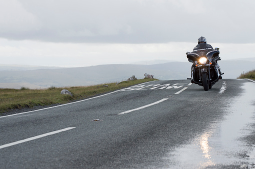 Swansea, Wales - August 2, 2014: Man on a Harley Davidson motorcycle, riding on a mountain road in the Black Mountains in Swansea. Part of a motorbike convention.