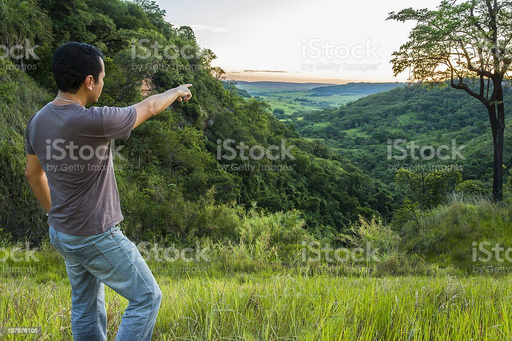 Man on a mountain pointing towards the sunset royalty-free stock photo