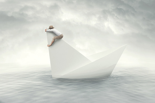 man on a paper sinking boat