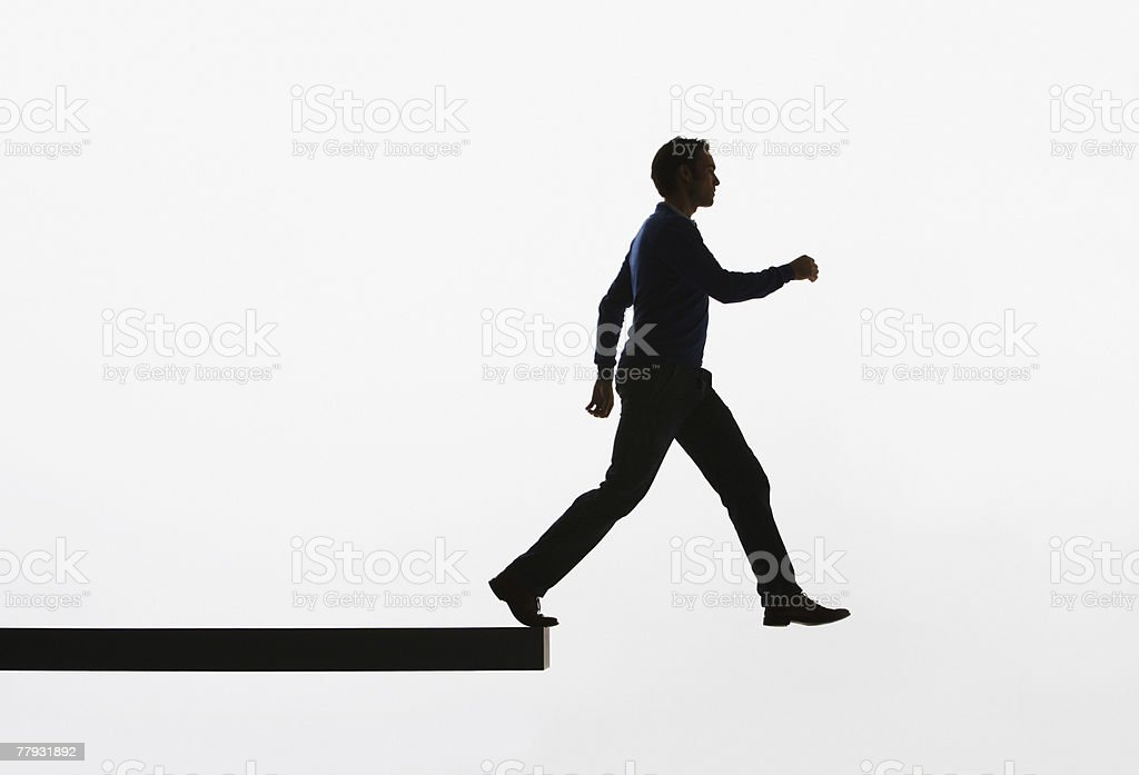Man on a plank about to walk over ledge stock photo
