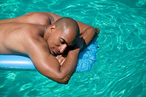 mann auf einer luftmatratze - traum pools stock-fotos und bilder