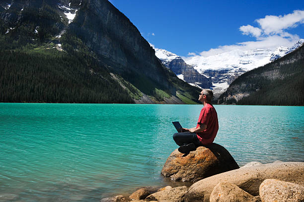 Man on a rock by the lake with mountains in the background stock photo
