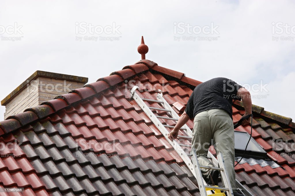Man on a roof, cleaning the tiles with pressure washer royalty-free stock photo
