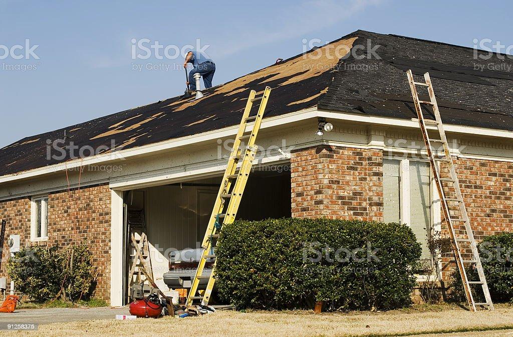 Man on a rooftop repairing tornado damaged shingles stock photo
