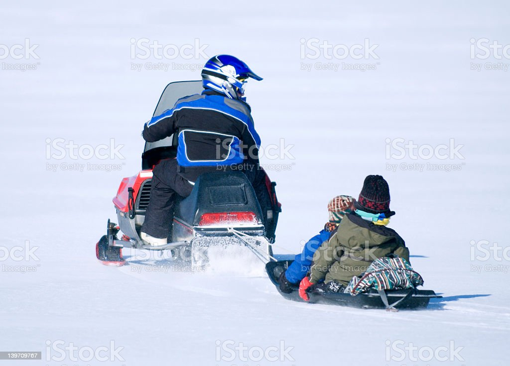 A man on a snowmobile pulling two small children behind him stock photo