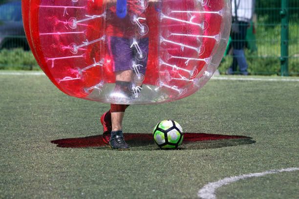 man on a sports field playing in the bumper ball stock photo