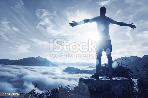 Man with spread arms standing in front of a mountain panorama.