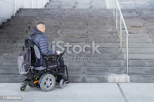 Disabled man with muscular dystrophy on an electric wheelchair who can't get up the stairs. Accessibility concept.
