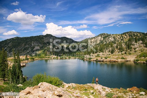 903015102 istock photo Man on an adventure exploring a lake and walking a suspension bridge 903015070