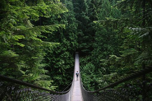 Man on an adventure exploring a lake and walking a suspension bridge
